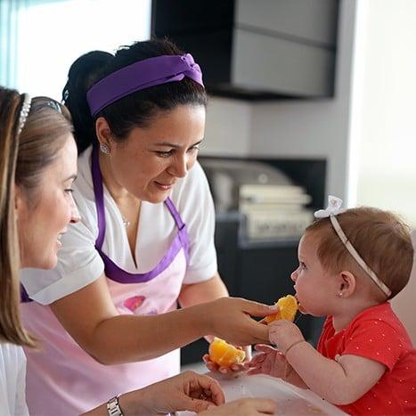 paula-stancari-ensinando-uma-mae-a-oferecer-laranja-para-o-bebe-durante-a-introducao-alimentar